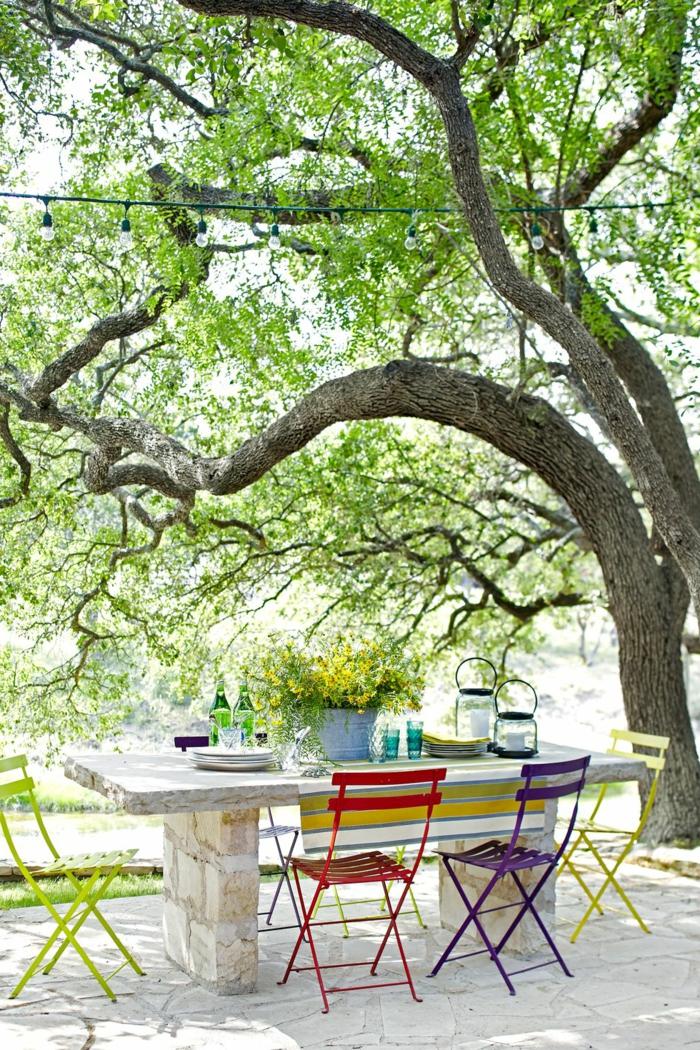 jardines modernos decorados con estilo, grande mesa con sillas de madera pintadas en diferentes colores