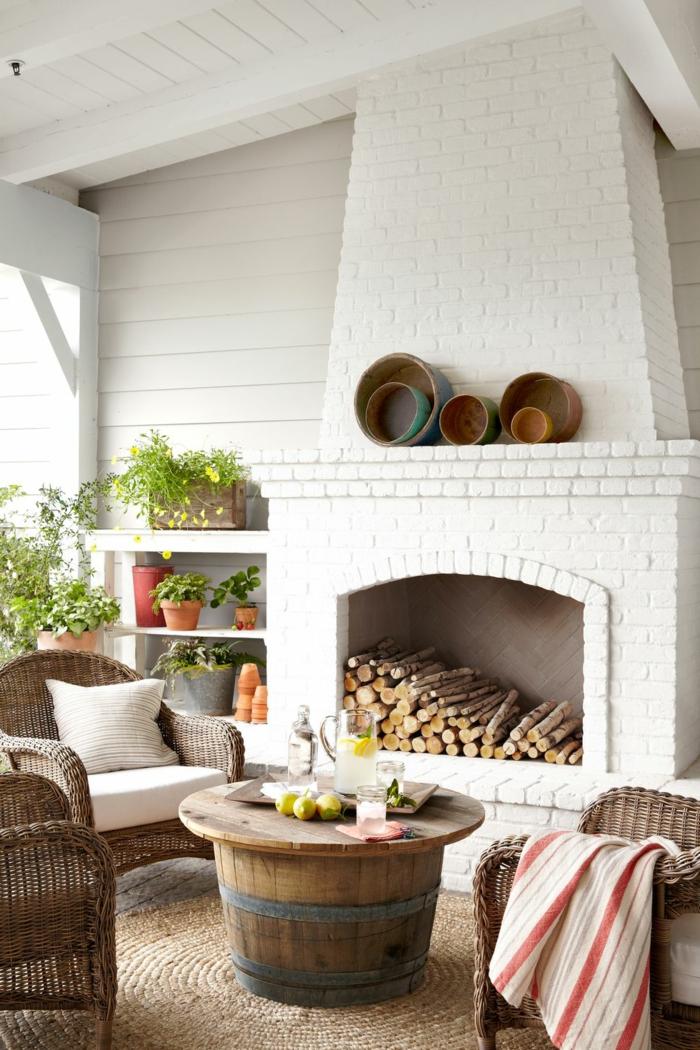 bonita decoración de jardines rusticos y terrazas, muebles de madera y mimbre, chimenea de leña en blanco