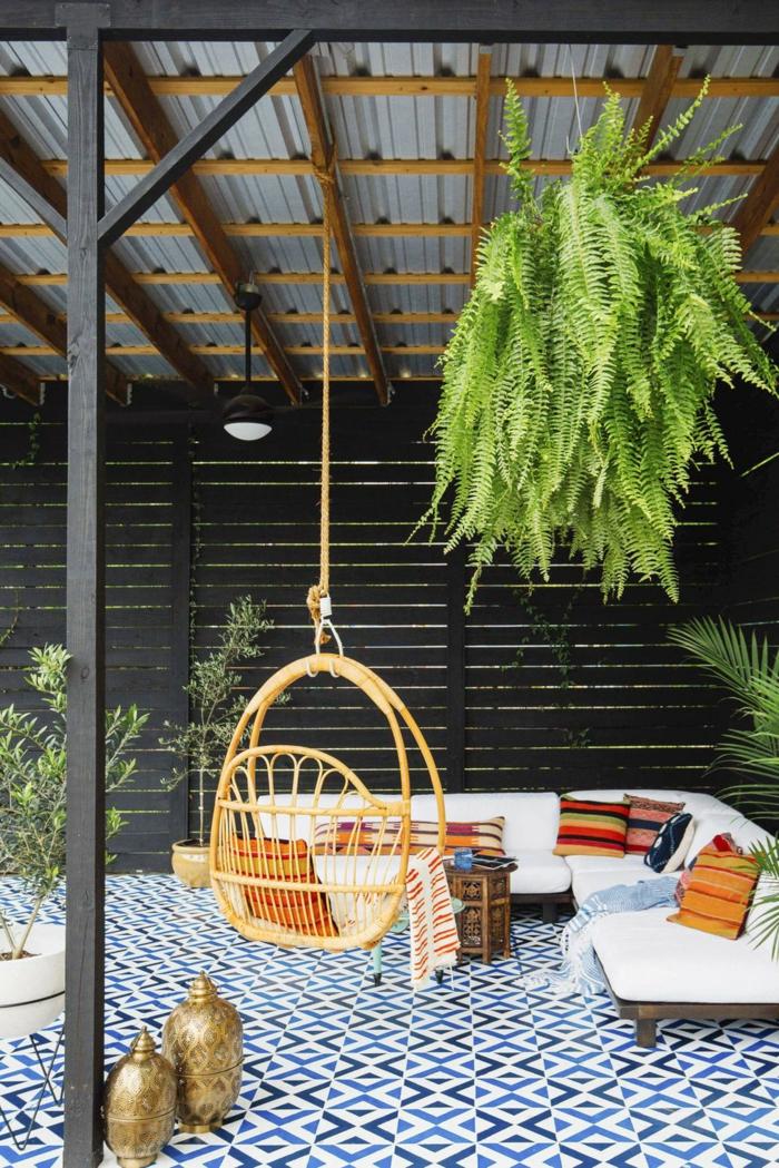 ideas de decoracion esxteriores, bonita silla de madera colgante, suelo con azulejos ornamentados en blanco y azul, macetas colgantes