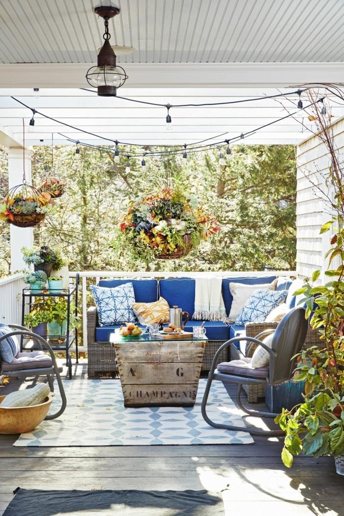 ideas de encanto decoracion porches , porche moderno con guirnalda de bombillas, muebles en tonos oscuros y cojines en blanco y azul
