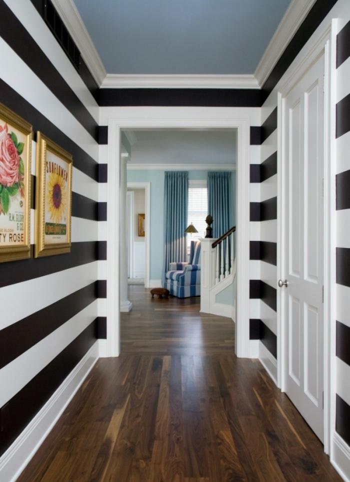 paredes con papel pintado en blanco y negro y suelo de parquet, como decorar un pasillo largo con cuadros decorativos