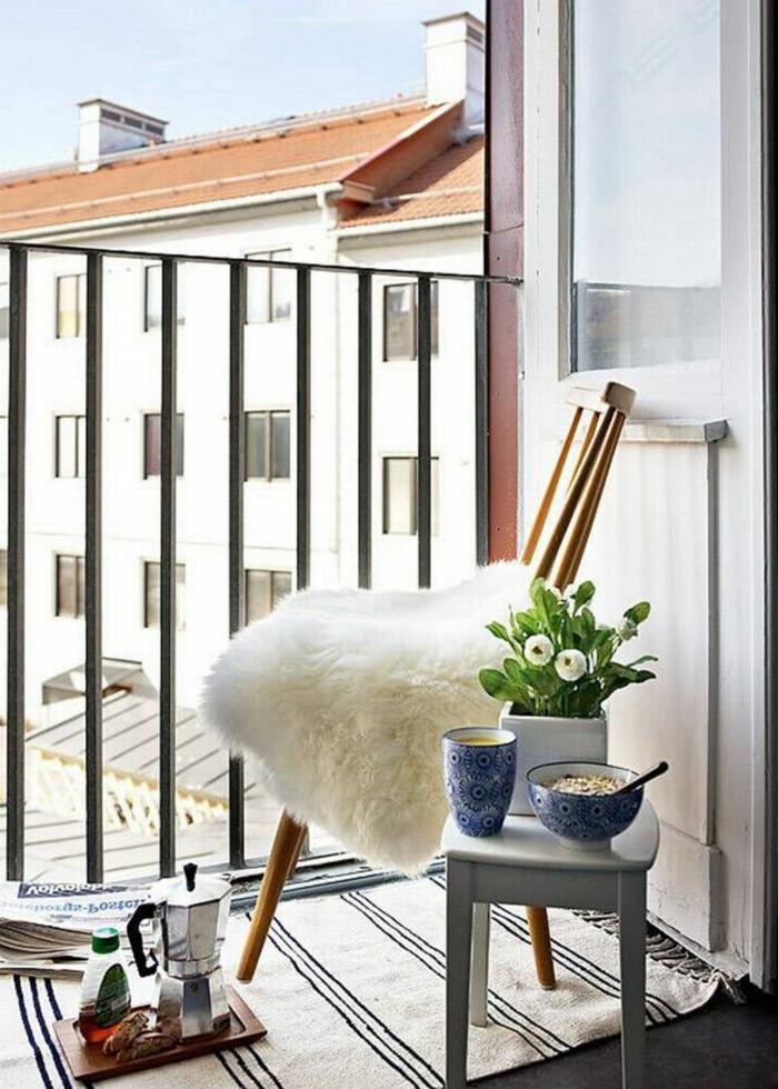 ideas y trucos en la decoración de terrazas pequeñas, silla de madera con manta peluda en blanco alfombra en rayas