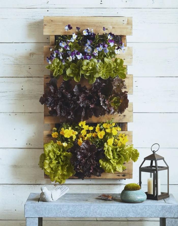 jardineras con palets DIY para decorar la casa, jardinera vertical de madera con macetas de lechuga y flores