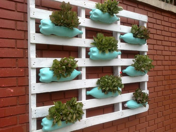 jardineras con palets originales para decorar la casa, palet pintados en blanco decorado con botellas de plástico con plantas verdes
