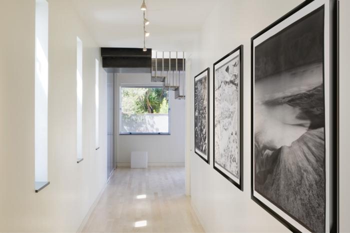 pasillo moderno en blanco con suelo de parquet y decoración de cuadros decorativos en blanco y negro, ideas sobre como decorar un pasillo largo