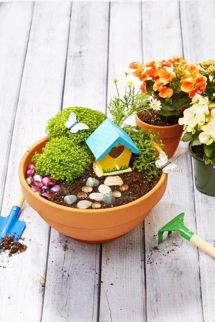 originales ideas para decorar jardines, macetero de arcilla con pequeñas plantas verdes y decoración de figuras de madera