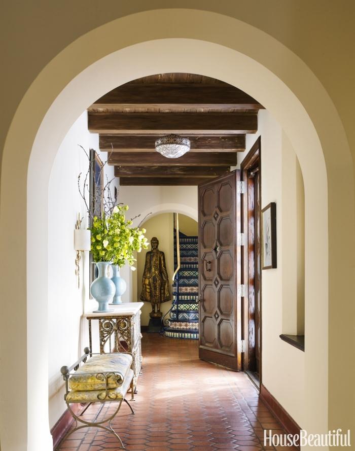 cómo decorar un pasillo largo en beige y marrón, banco tapizado en amarillo y gris, muebles vintage y techo con vigas de madera