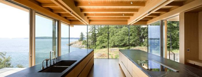 cocinas con isla modernas en estilo minimaslita, largas islas con barra y techo de vigas de madera