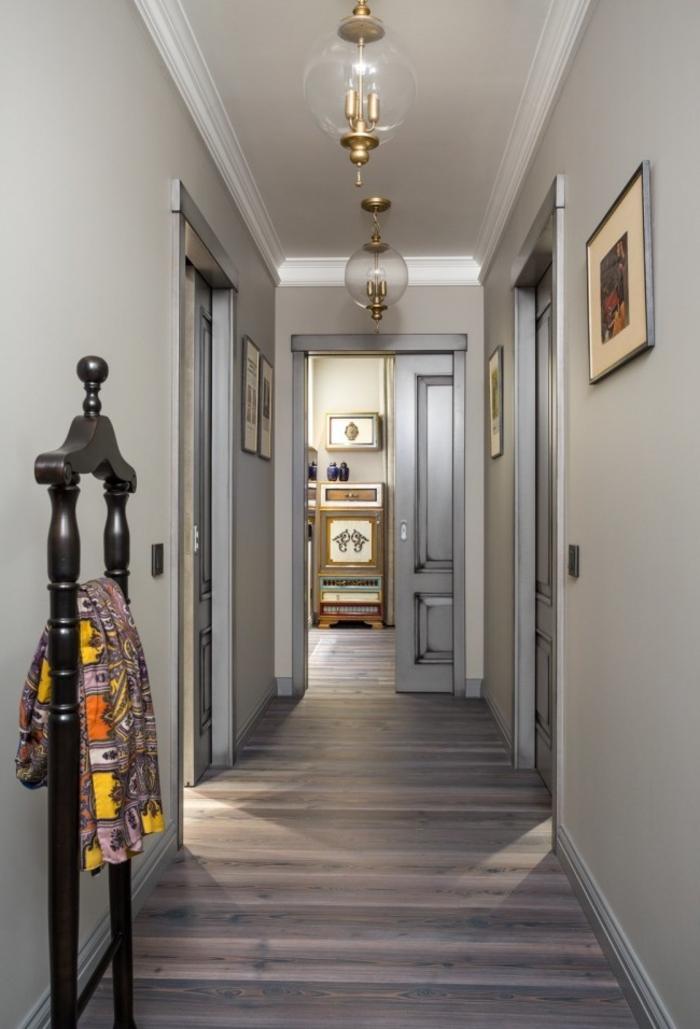 ideas originales sobre cómo decorar un pasillo largo, paredes en beige y gris, suelo de parquet y detalles decorativos