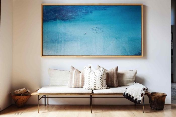 decoracion en estilo bohemio, corredor con grande pintura en la pared, banco de madera y cojines decorativos, cómo decorar un pasillo largo