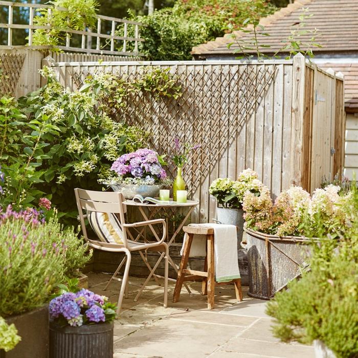 ejemplos de decoracion terrazas y patios, peque;as mesa y sillas de madera, plantas verdes con flores