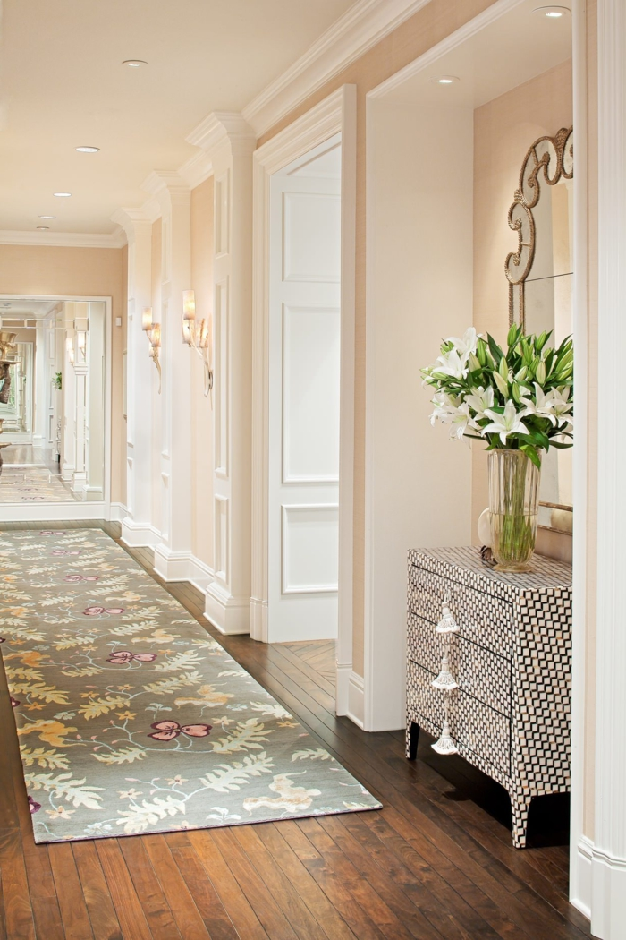 pasillo largo y bien iluminado en tonos claros, alfombra en gris con motivos florales y suelo de parquet, cómo decorar un pasillo largo según las últimas tendencias