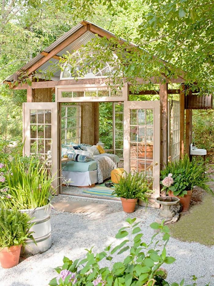 ideas de patios con encanto, pergola de madera abuhardillada, muchas plantas verdes en maceteros y flores decorativos