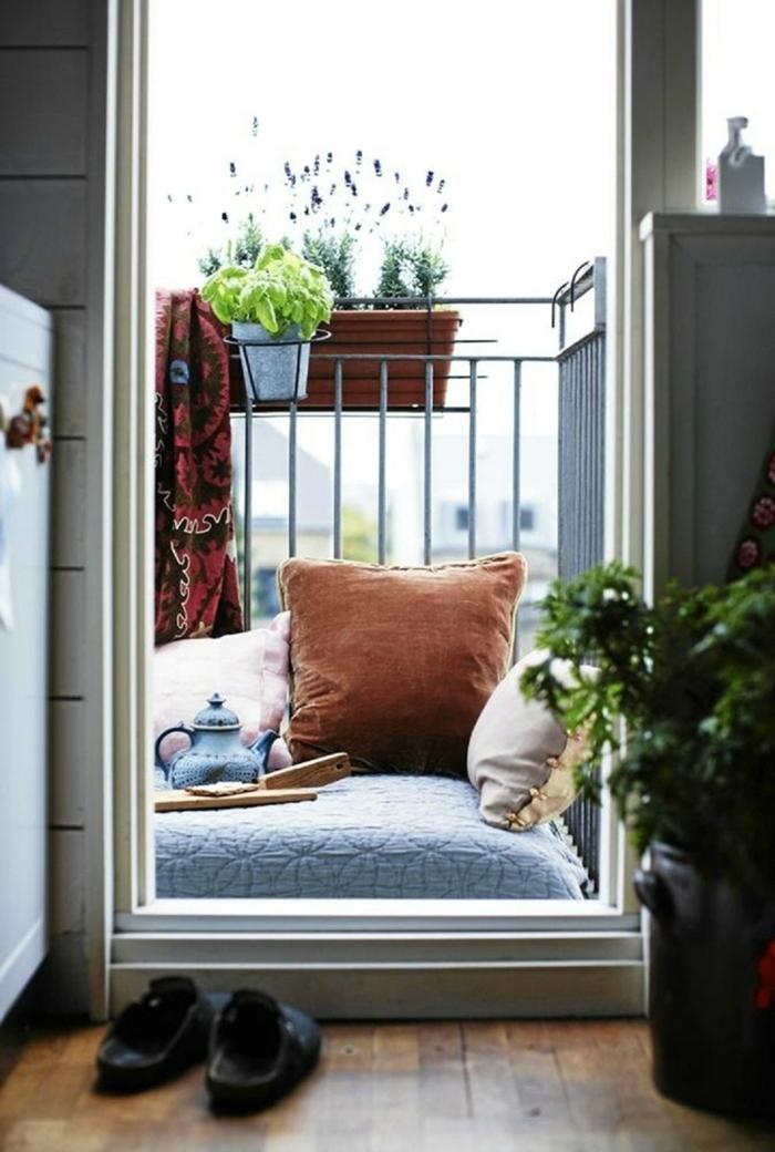 precioso rincón de relax en un balcón pequeño, cojines decorativos y macetas platnas verdes, decoracion de terrazas 2018