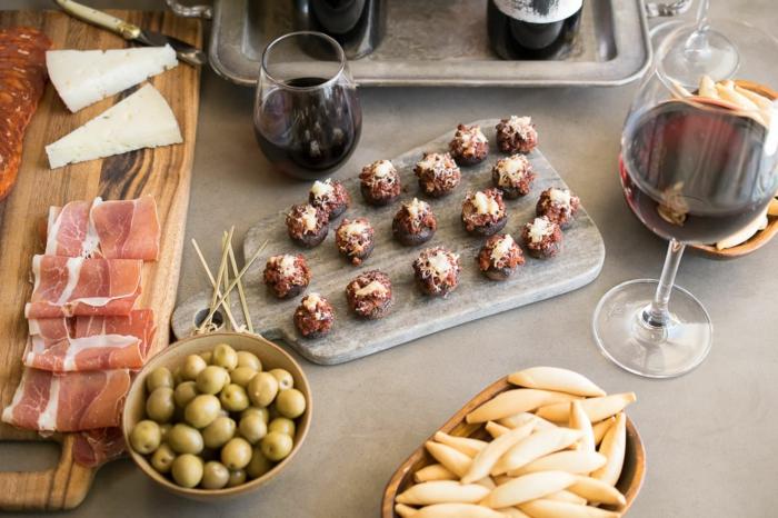 tapas sabrosas con vino tinto, setas rellenas de chorizo y queso, aceitunas verdes y jamón ibérico