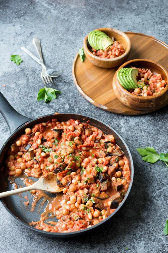 tapas fáciles, ricas y rápidas, caserola con garbanzos, berenjenas y salsa de tomate adornada con rebanadas de aguacate