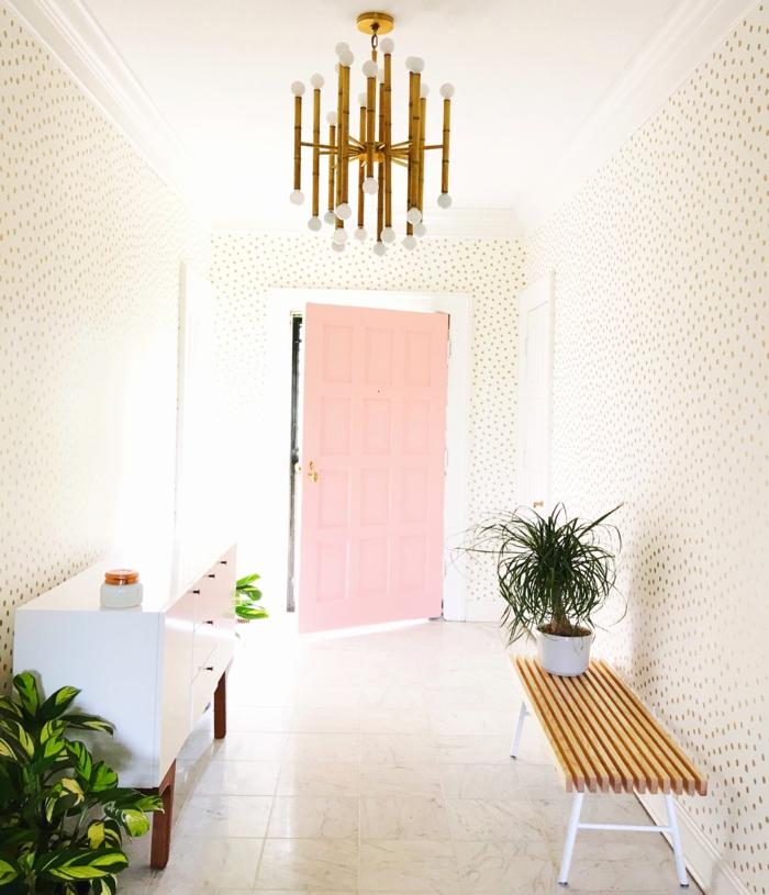 decoracion pasillos de encanto, paredes con papel pintado claro, decoración de plantas verdes y puerta en rosado