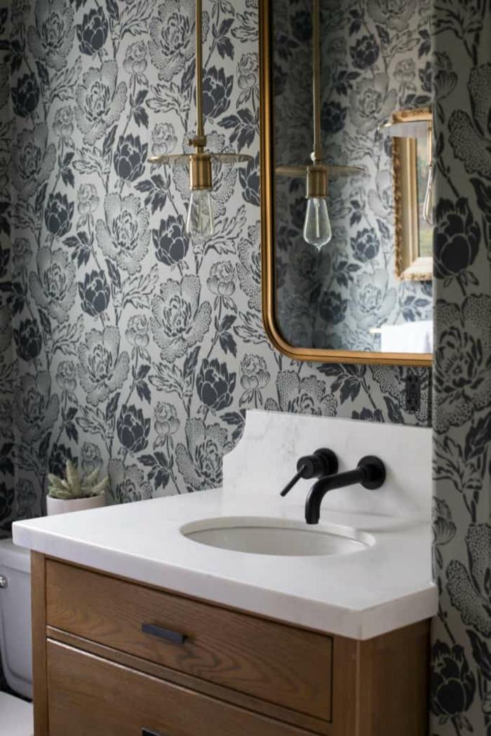 baño decorado de encanto con papel pintado salon estampados de rosas, espejo con marco dorado y lámparas modernas