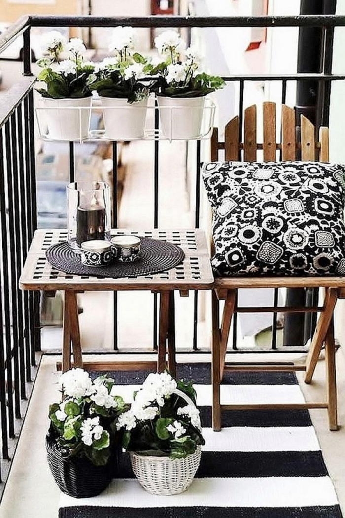 decoracion balcones pequeños en blanco y negro, pequeños muebles de madera y macetas de mimbre con flores blancas
