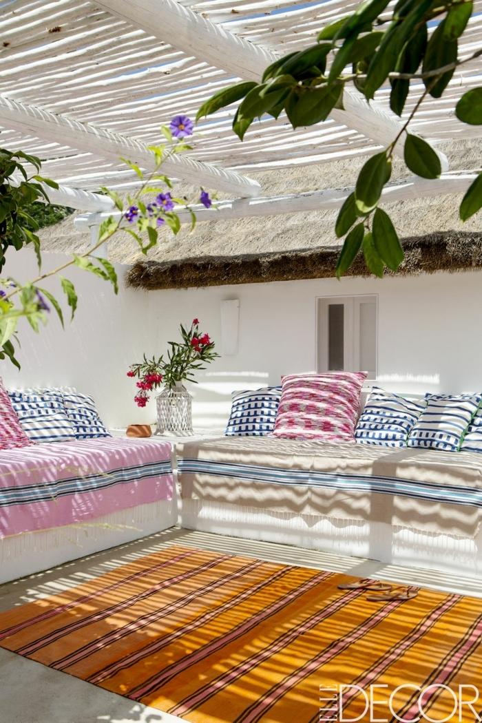patios decorados n estilo africano, precioso diseño con cojines decorativos en blanco, rojo y azul