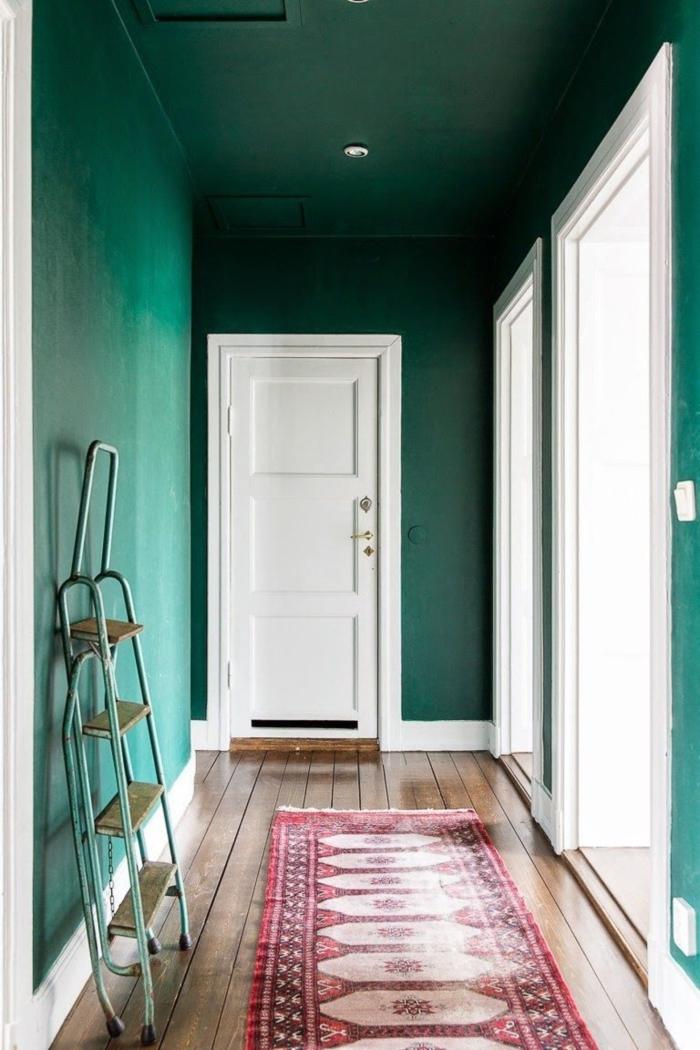ideas de decoracion pasillos, corredor largo con paredes en verde saturado, suelo de parquet y alfombra en rojo y beige