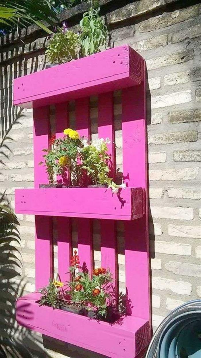 jardin vertical con palets pintado en rosado y colgado en la pared, pequeñas macetas colocadas en los estantes