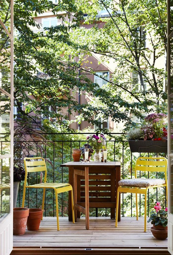 ideas de decoracion de terrazas y balcones pequeños, mesa de madera y dos sillas en color amarillo