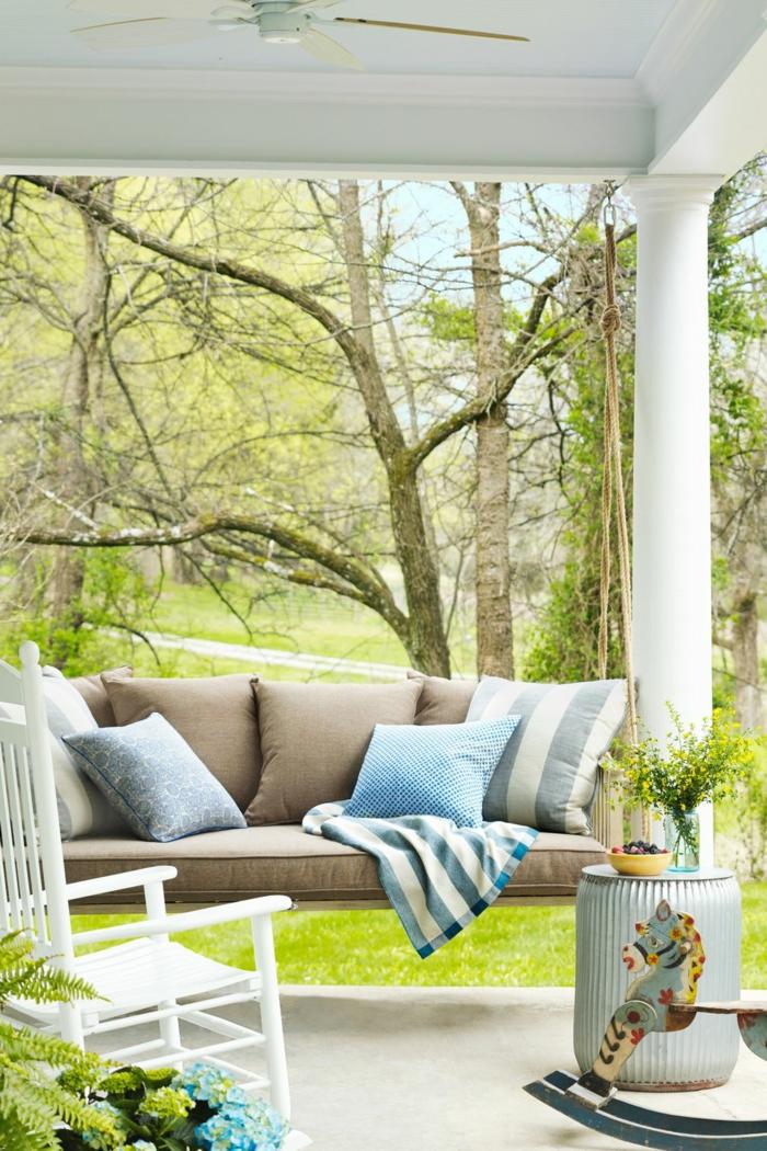 ideas para jardines y patios, terraza decorada en tonos claros, sofá en beige con cojines decorativos en azul y blanco