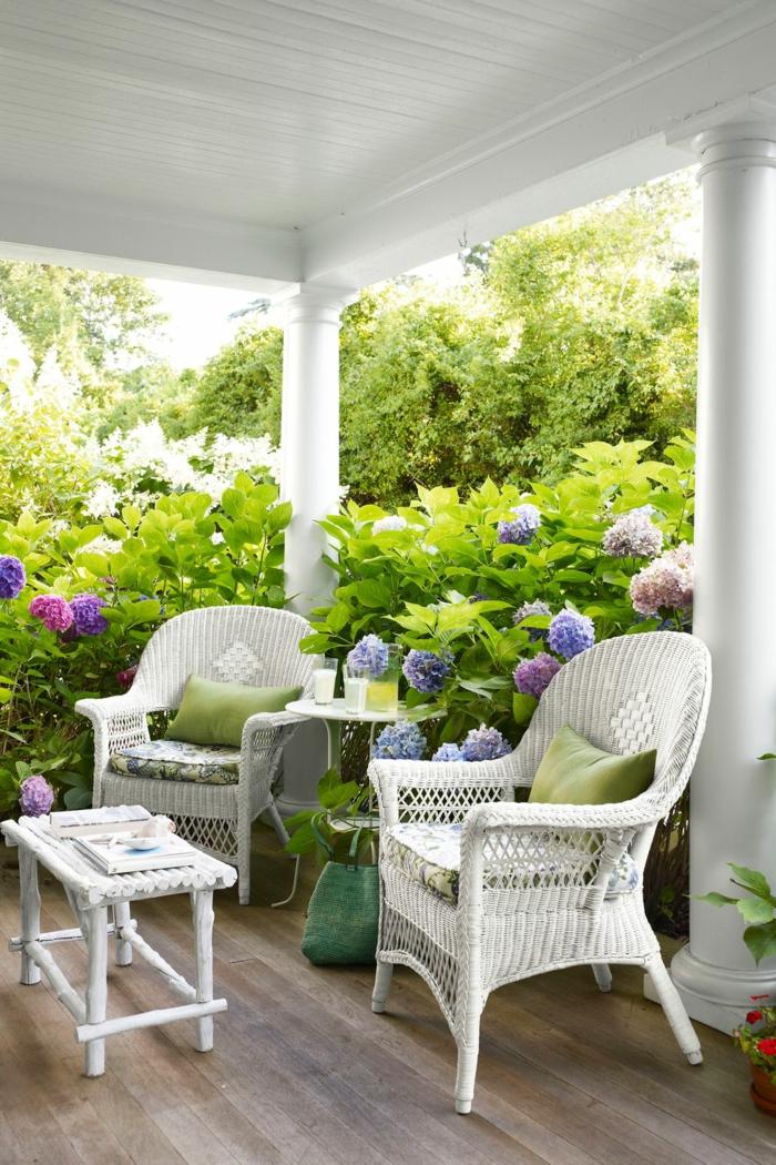 ideas moderna de decoracion porches y patios, sillas vintage y pequeña mesa en blanco, suelo de parquet y grandes arbustos