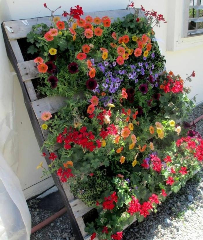 ejemplos de maceteros de palets DIY con flores coloridos, lecho de flores para decorar tu patio