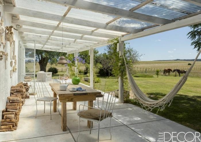 patios con encanto decorados en colores claros, suelo de baldosas grandes, hamaca de encanto y bonita vista