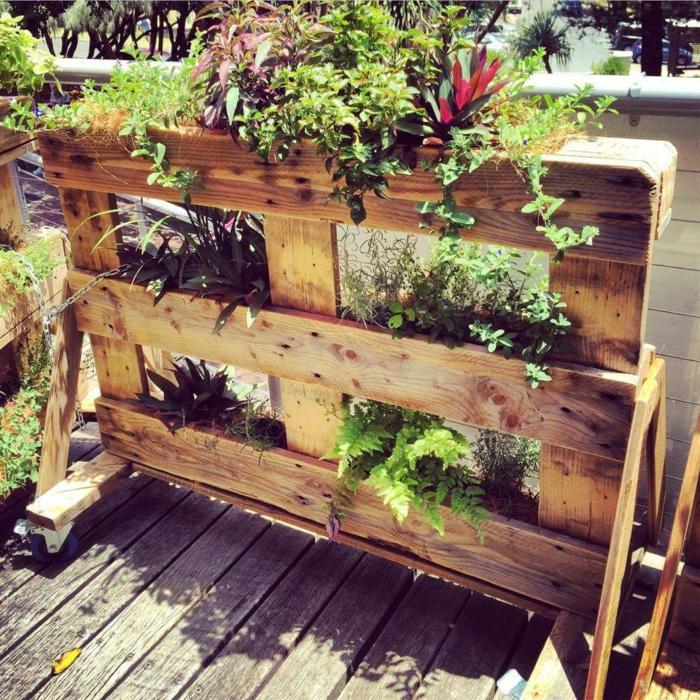 maceteros de palets con ruedas con pequeñas macetos, ideas de jardineras de madera para el patio