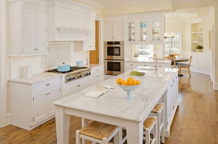 cocinas pequeñas con isla decoradas en blanco, larga isla con sillas altas, suelo de parquet y armarios funcionales