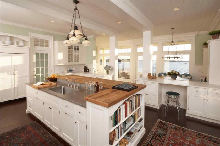 ejemplos de cocinas blancas modernas con grande isla con lavabo, armarios, barra de madera y estantes con libros