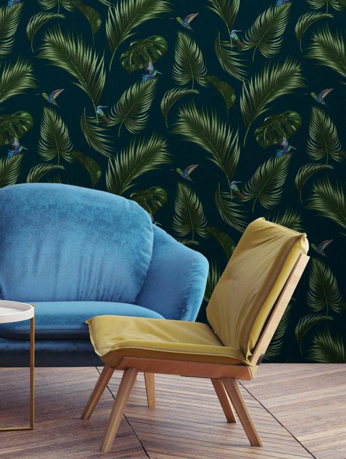 combinación de colores sofisticada, silla en color mostaza, sofá tapizada en azul y papel pintado habitacion con estampado de hojas