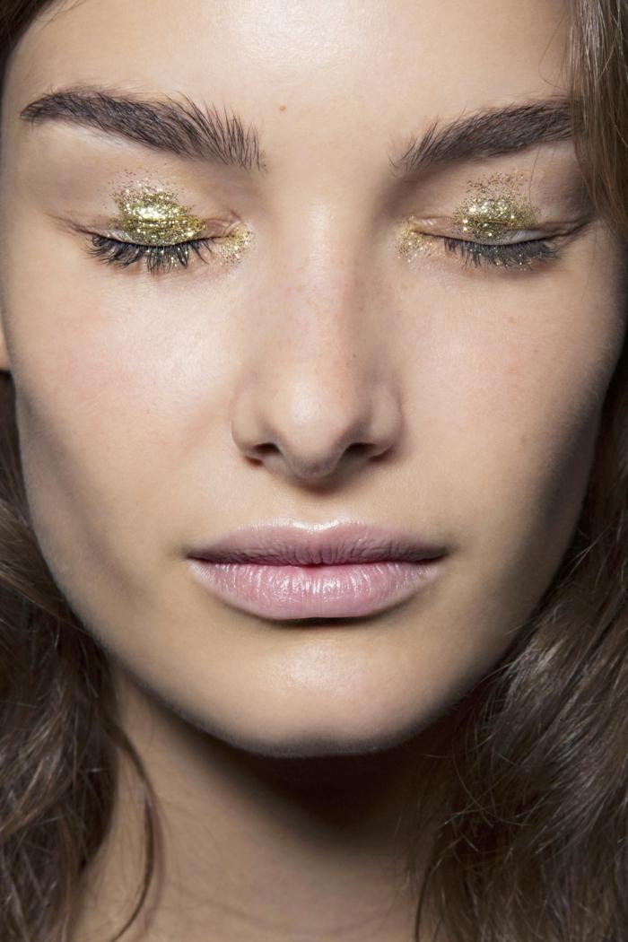 sombras en dorado con partículas relucientes y labios con tinte en rosado efecto mojado, como maquillar ojos tendencias 2018
