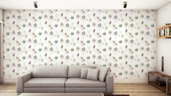 salón decorado en estilo minimalista con papel pintado en blanco y dibujos de aves, sofá en gris y suelo de parquet