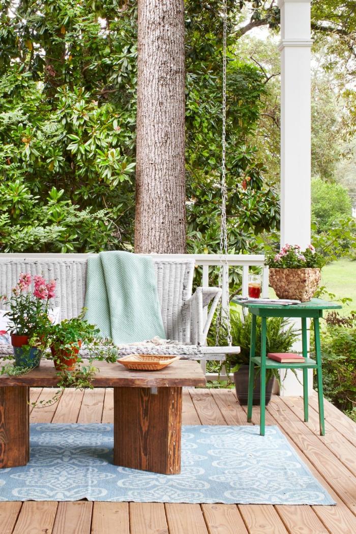 ideas bontas decoracion de jardines con piedras, mesa baja de madera de diseño original, suelo de madera y alfombra en azul claro y blanco