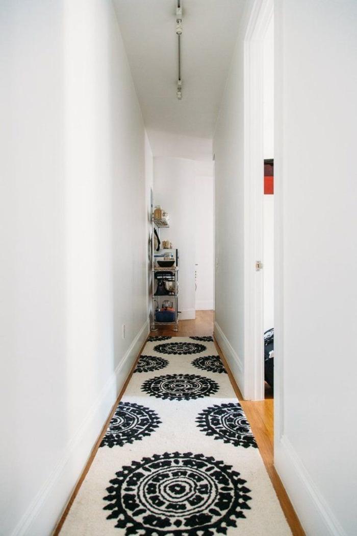 decorar pasillos estrechos con estilo, alfombra ornamentada en blanco y azul oscuro, paredes en blanco y suelo de parquet