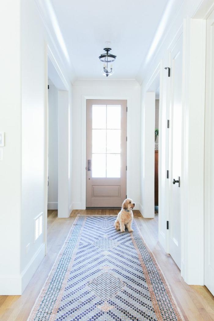 preciosa decoracion en tonos claros pastel, alfombra ornamentada, suelo de parquet y paredes en blanco