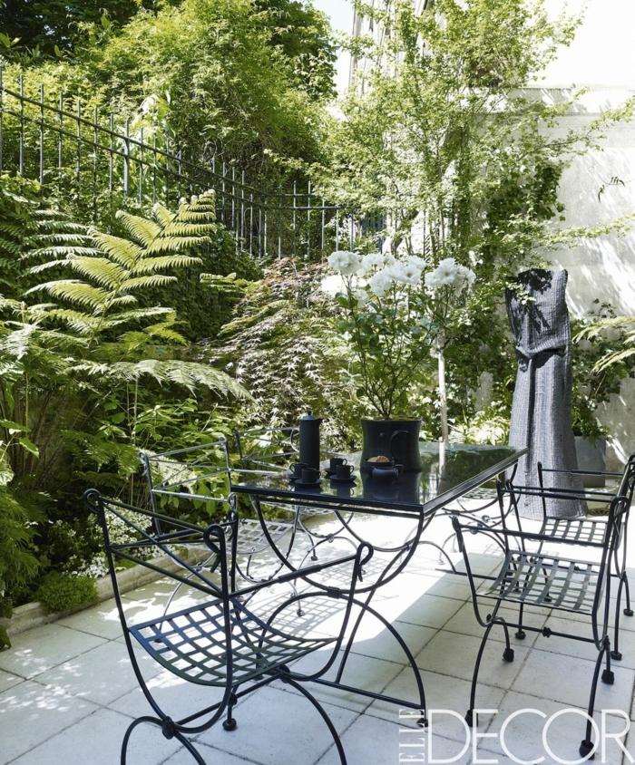 patios ideas para jardines pequeños, sillas y mesa negros de metal, plantas y arbustos altos