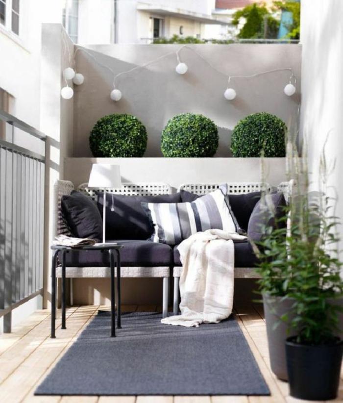 decoracion de terrazas con guirnaldas de luces y arbustos ornamentales, mueble de diseño en beige y negro