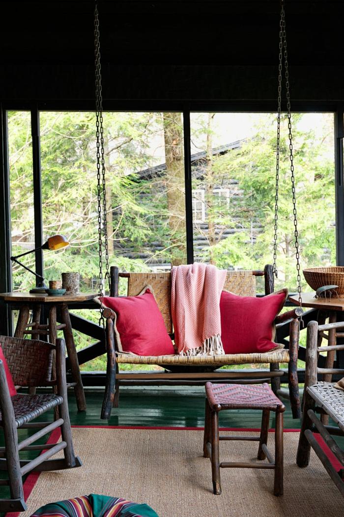 decoracion exteriores moderna, muebles de diseño en colores oscuros, banco colgante moderno con cojines decorativos en rojo