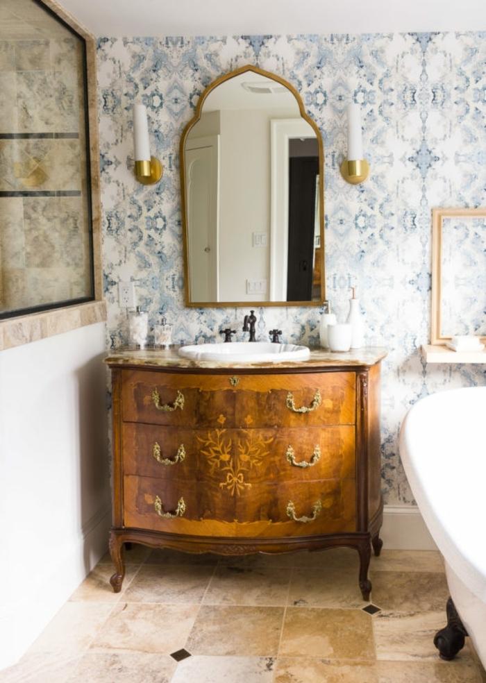 precioso baño en estilo vintage con papel decorativo para pared en azul y blanco, cofre oranamentado de madera y bañera patas garra