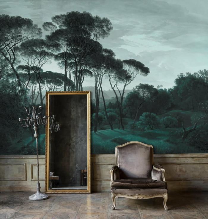 decoración en estlo vintage con papel decorativo para pared retro, espejo de marco dorado apoyado en la pared y muebles vintage