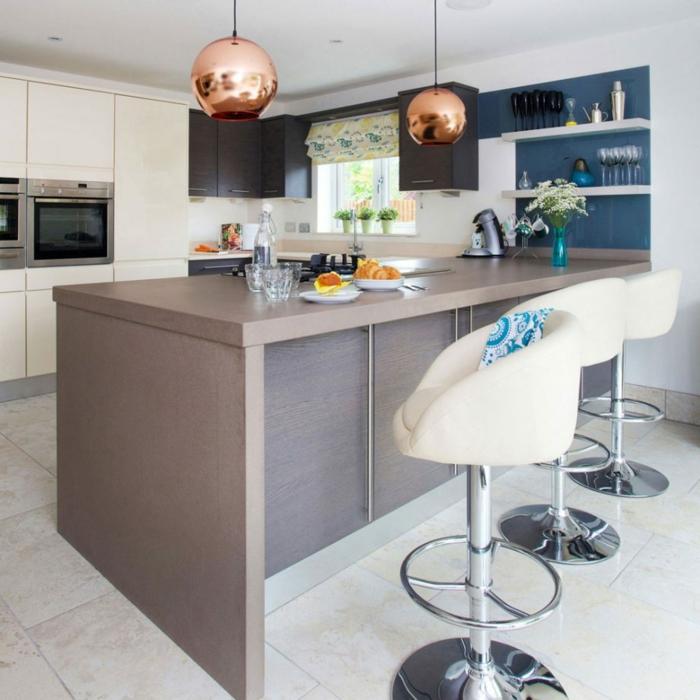 diseños de cocinas modernas, grande isla barra, sillas modernas en blanco y lámparas en color cobrizo