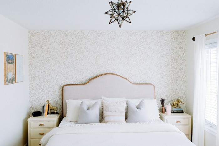 dormitorio matrimonio decorado en tonos claros pastel, cama con capitoné y paredes con papel para forrar muebles y paredes