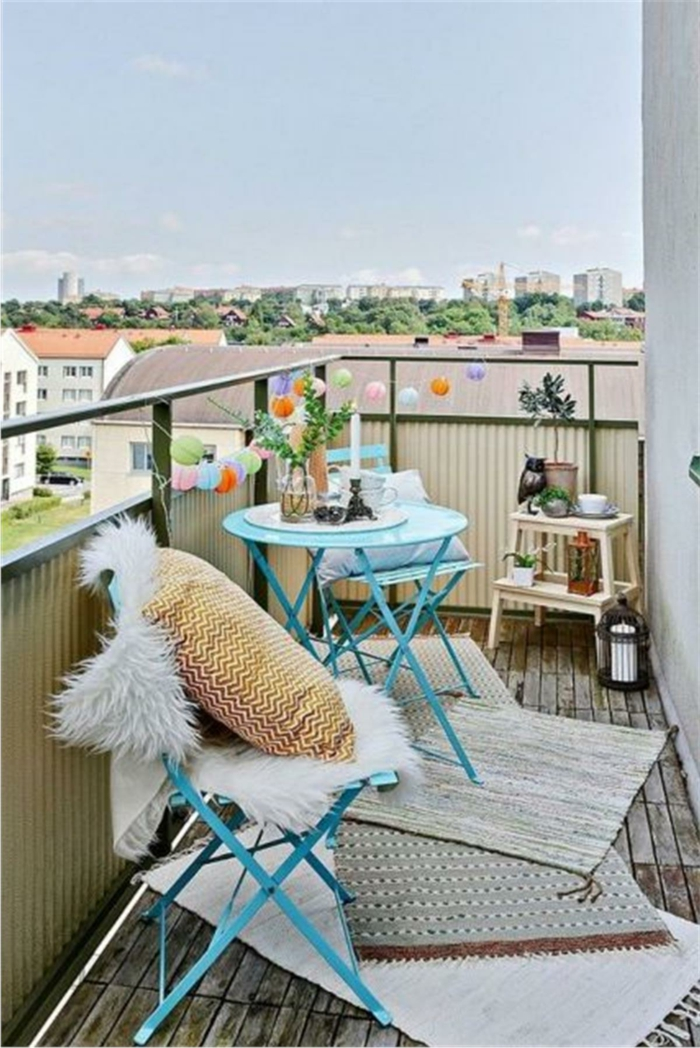 decoracion balcones pequeños colores claros, muebles plegables pintados en azul y alfombras en beige