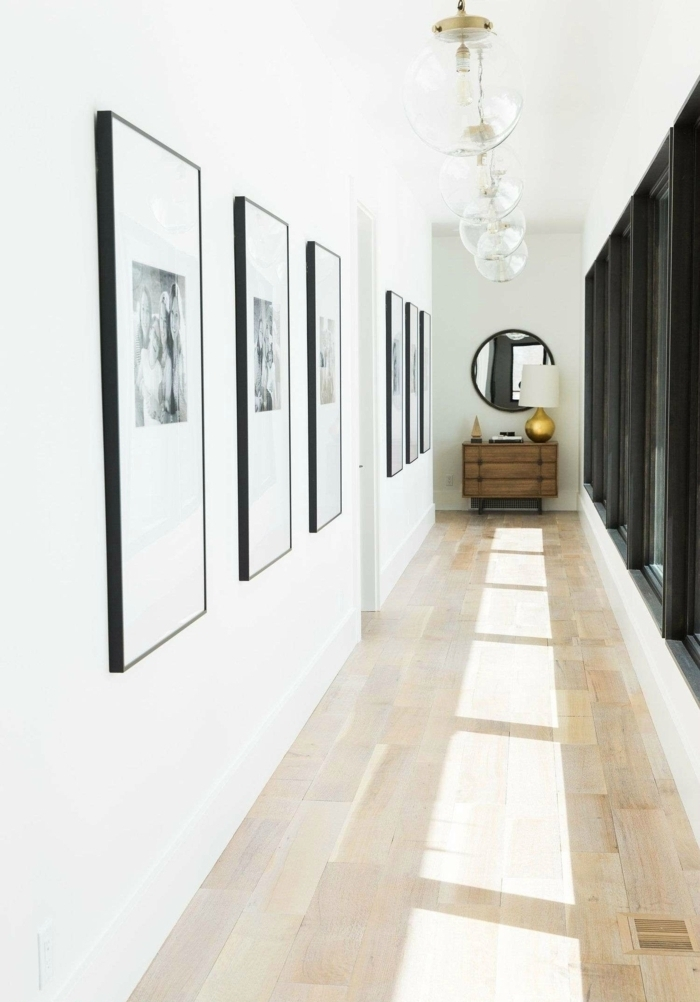 grande corredor con paredes en blanco adornadas de cuadros decorativos, fotografías en blanco y negro, ideas sobre como decorar un pasillo largo