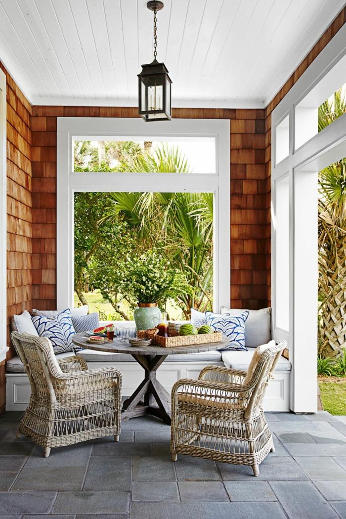 precioso porche decorado en estilo moderno con sillones de ratán y cojines decorativos, decoracion de jardines con piedras